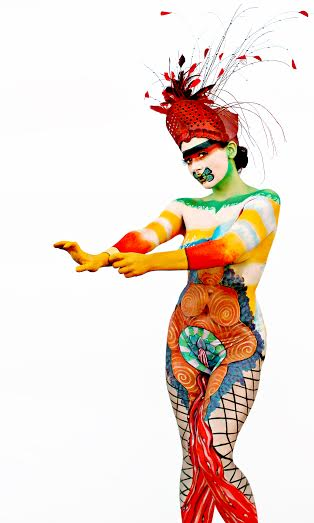 "Venus By Deborah Brommer This body painting shows the many dichotomies of women in the modern world and her place as goddess/slave, mother/whore, beauty/untouchable. The Stone Age ""Venus of Willendorf"" is a reminder of the age old reverence of woman as creator of life, yet throughout time women have been virtually slaves to the men in their lives as is represented here by the yellow rubber gloves of housework. We want our women to have a beautiful face, and a sexy demeanor, yet they must, in some societies cover up in public and keep quiet on matters of importance and we see that here with the strip across the eyes painted as a ""reverse burka"". Her mouth is silenced by a bumble bee with the wings of a moth; the bee represents hard work and dedication and the moth is representative of transformation as well as the subtle meaning of always flying to the light which shows undying optimism. Covering our model's sex organs is a beautiful flower (an homage to feminist artist Judy Chicago) which is lovely and beckoning, yet from that same flower flows rivers of blood which shows our lunar biology which has kept women separated, and shunned, and proclaimed ""dirty"" in many societies, but is actually the literal life blood of our species."